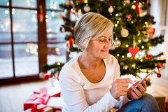 Senior woman in front of Christmas tree. Inside the house, with smartphone, texting Royalty Free Stock Photos