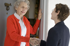 Senior woman at front door. Attractive senior woman shaking hands with visitor at her front door Royalty Free Stock Images