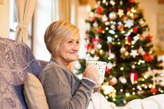 Senior woman in front of illuminated Christmas tree. Beautiful senior woman sitting on couch in front of illuminated Christmas tree inside in her house enjoying Royalty Free Stock Photography