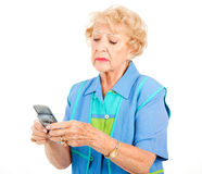 Senior Woman Frustrated by Texting. Senior woman trying to text and getting frustrated.  Isolated on white Stock Photo