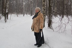 Senior woman fur coat and hat standing in cold winter snow covered forest Royalty Free Stock Photography