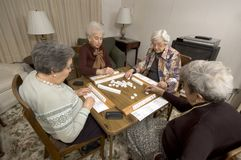 Senior woman at the game table. Group of happy senior women playing mah-jong with friends Royalty Free Stock Photos