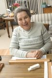 Senior woman at the game table. Happy senior woman playing mah-jong with friends Stock Images