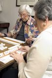 Senior woman at the game table. Happy senior women playing mah-jong with friends Royalty Free Stock Image
