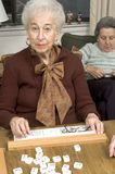 Senior woman at the game table. Happy senior woman playing mah-jong with friends Stock Photo