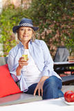 Senior woman in garden with champagne Royalty Free Stock Photo