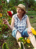 Senior woman is gardening in her garden Royalty Free Stock Photography