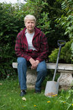 Senior  woman gardening. Senior woman gardening, sitting with spade Royalty Free Stock Photography
