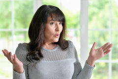 Senior woman gestures. Portrait of a senior woman gestures at home Royalty Free Stock Photos
