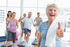 Senior woman gesturing thumbs up with people exercising Royalty Free Stock Images