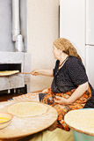 Senior woman gets a bread from the oven Stock Photo