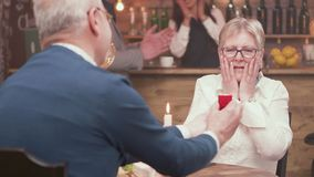Senior woman gets very emotional when her partner makes a marriage proposal. Old woman being asked to get married. Engagement ring stock video