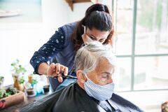 Free Senior Woman Getting A Haircut At Home During Covid-19 Pandemic Wearing Face Mask Stock Image - 183331521