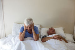 Senior woman getting disturbed with man snoring on bed Royalty Free Stock Photography