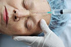 Senior woman getting on face injection Royalty Free Stock Photos