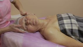 Senior woman getting face massage in spa salon stock footage