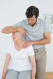Senior woman getting the neck adjustment done Royalty Free Stock Photo