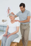 Senior woman getting the neck adjustment done Royalty Free Stock Photos