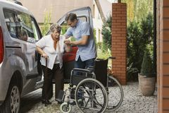 Senior woman getting out of the car with the help of a nurse stock photos