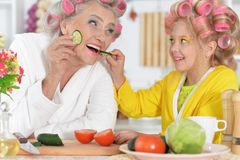 Senior woman and girl with pink hair curlers on head stock photo