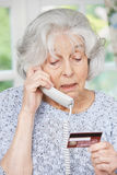 Senior Woman Giving Credit Card Details On The Phone. Senior Woman Giving Credit Card Details Over The Phone royalty free stock photos