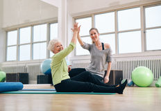 Senior woman giving high-five to her personal trainer Royalty Free Stock Photography