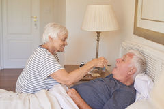 Senior woman giving medicine to her sick husband in bed Stock Images
