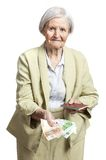 Senior woman giving money and holding passport Royalty Free Stock Images