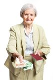 Senior woman giving money and holding passport Stock Photo