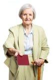 Senior woman giving passport over white background Stock Photos