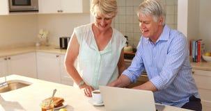 Senior woman giving tea to senior woman in kitchen. At home