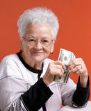 Senior woman in  glasses holding money Royalty Free Stock Photos