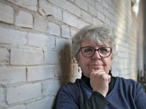 Senior woman with glasses looking past camera thoughtfully royalty free stock photography