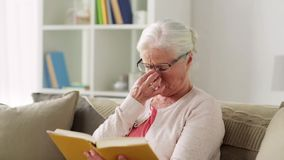 Senior woman in glasses reading book at home stock video