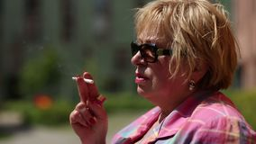 Senior woman with glasses smoking a cigarette. Female smoker stock footage