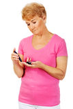 Senior woman with glucometer checking blood sugar level Stock Photos