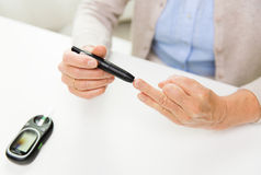Senior woman with glucometer checking blood sugar Royalty Free Stock Photos