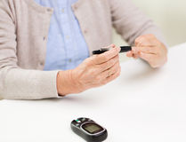 Senior woman with glucometer checking blood sugar. Medicine, age, diabetes, health care and people concept - close up of senior woman with glucometer checking stock photos