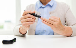 Senior woman with glucometer checking blood sugar Stock Photos