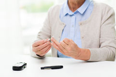 Senior woman with glucometer checking blood sugar Royalty Free Stock Photography