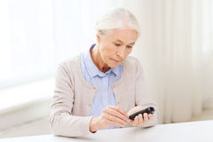 Senior woman with glucometer checking blood sugar Stock Images