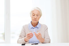 Senior woman with glucometer checking blood sugar Royalty Free Stock Images