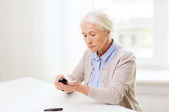 Senior woman with glucometer checking blood sugar Royalty Free Stock Image