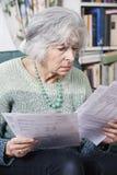 Senior Woman Going Through Bills And Looking Worried Stock Photos