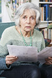 Senior Woman Going Through Bills And Looking Worried Royalty Free Stock Photography