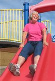 Senior woman going down a slide Royalty Free Stock Photos