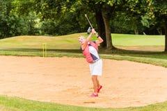 Senior woman at golf having stroke in sand bunker Stock Image