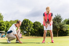 Senior woman and golf pro practicing their sport stock photo