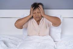 Senior woman got a headache on bed. Senior woman got a headache on a bed Royalty Free Stock Photography