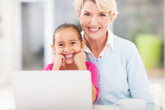Senior woman grandchild. Pretty senior women and her grandchild in front of laptop looking at the camera stock images